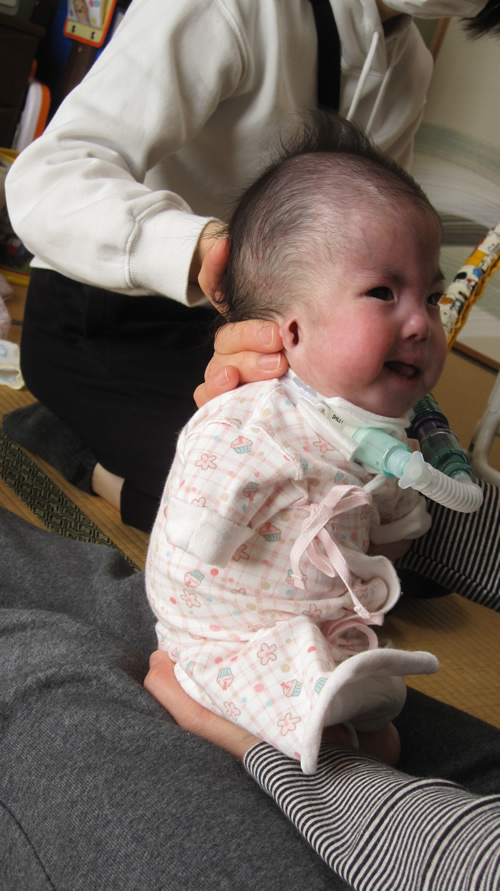 看護師が呼吸器を補助しながら、母の抱っこで遊ぶ様子